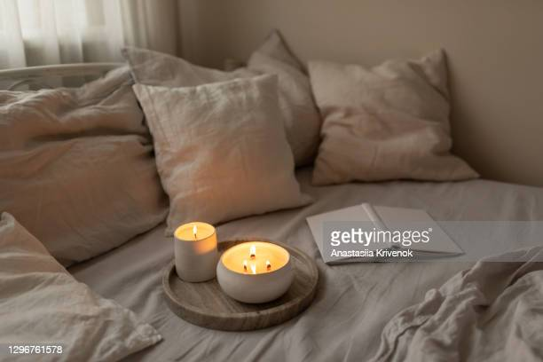 scented candles in ceramic bowls on linen bed with book at home. - book stock pictures, royalty-free photos & images