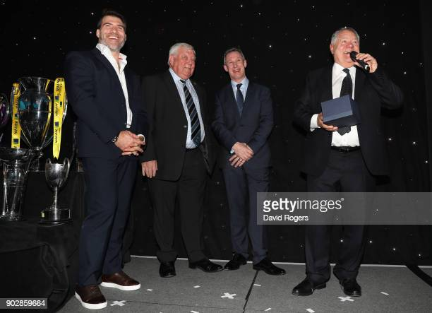 Schalk Brits of Saracens Tony Rowe owner of Exeter Chiefs and Rob Howley Lions assistant coach look on as Max Boyce talks to the audience after...