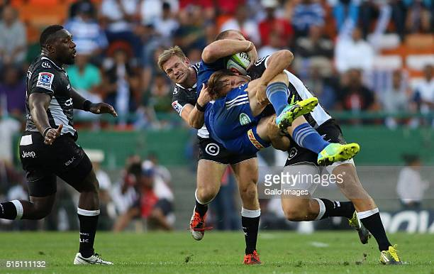 Schalk Burger of the Stormers is tackled by Paul Jordaan of the Sharks during the 2016 Super Rugby match between DHL Stormers and Cell C Sharks at...