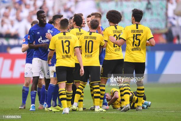 Schalke 04 players and Borussia Dortmund players clash as Achraf Hakimi of Borussia Dortmund goes down injured during the Bundesliga match between FC...
