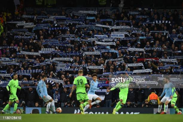 Schalke fans raise their scarves in the crowd during the UEFA Champions League round of 16 second leg football match between Manchester City and...
