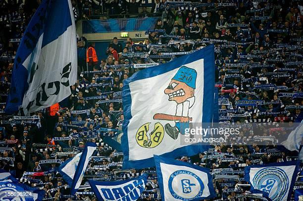 Schalke fans wave their flags during the UEFA Champions league group B football match between Schalke 04 and Arsenal in Gelsenkirchen on November 6...