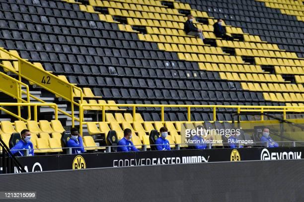 Schalke substitute players sit on the bench during the German Bundesliga soccer match between Borussia Dortmund and Schalke 04 in Dortmund, Germany.