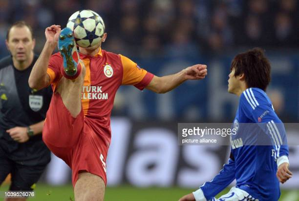 Schalke's Atsuto Uchida and Nordin Amrabat of Galatasaray vie for the ball during the UEFA Champions League round of 16 second leg soccer match...