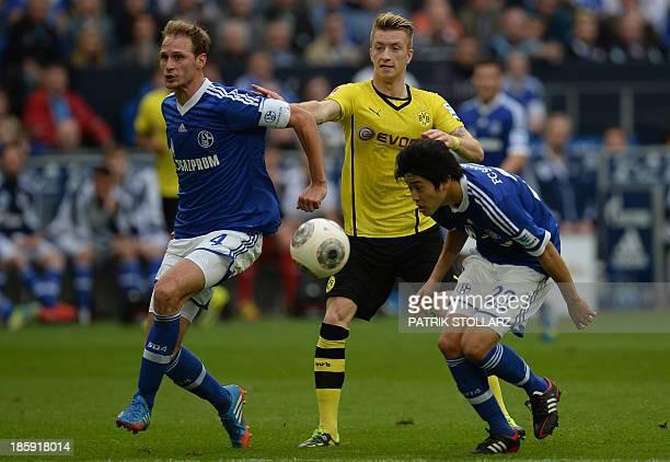 Schalke's defender Benedikt Hoewedes Schalke's Japanese defender Atsuto Uchida and Dortmund's striker Marco Reus vie for the ball during the German...