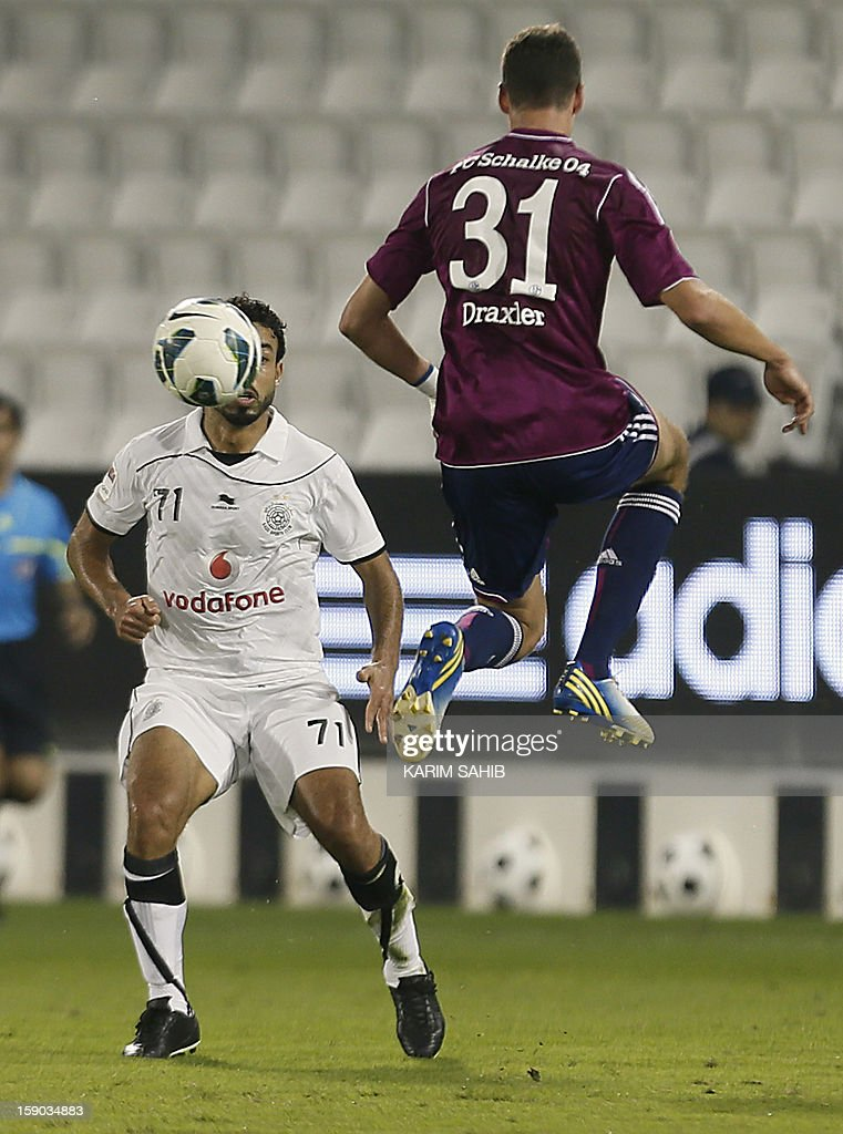 Schalke's Dutch striker Klaas-Jan Huntelaar (R) jumps for the ball as Al-Sadd's South Korean defender Lee Jung-Soo watches on during their friendly football match in Doha on January 6, 2013.