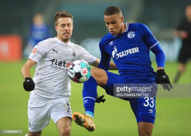 Schalke's Finnish midfielder Malick Thiaw and Moenchengladbach's German forward Patrick Herrmann vie for the ball during the German first division...
