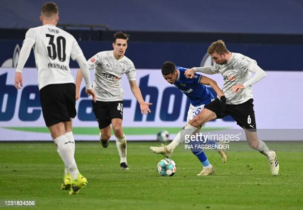 Schalke's French midfielder Amine Harit and Moenchengladbach's German midfielder Christoph Kramer vie for the ball during the German first division...
