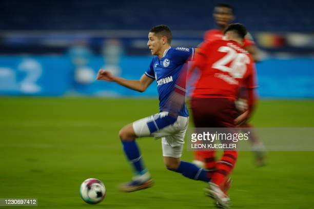 Schalke's French midfielder Amine Harit runs with the ball past Cologne's German defender Sava-Arangel Cestic during the German first division...
