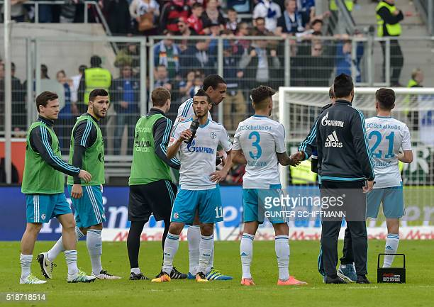 Schalke's FrenchMoroccan midfielder Younes Belhanda and his teammates stand on the pitch after the German first division Bundesliga football match FC...