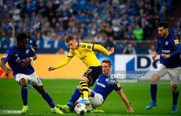 Schalke's German defender Bastian Oczipka and Dortmund's Belgian forward Thorgan Hazard vie for the ball during the German First division Bundesliga...