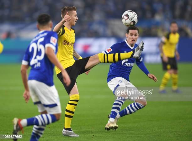 Schalke's German midfielder Sebastian Rudy and Dortmund's German forward Marco Reus vie for the ball during the German first division Bundesliga...