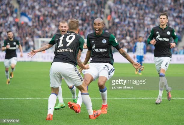 Schalke's goal scorer Guido Burgstaller is celebrated for his 20 by team mates Max Meyer und Naldo during the German Bundesliga soccer match between...