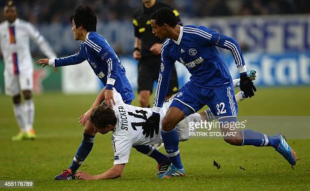Schalke's Japanese defender Atsuto Uchida Schalke's Cameroonian defender Joel Matip and Basel ´s midfielder Valentin Stocker vie for the ball during...
