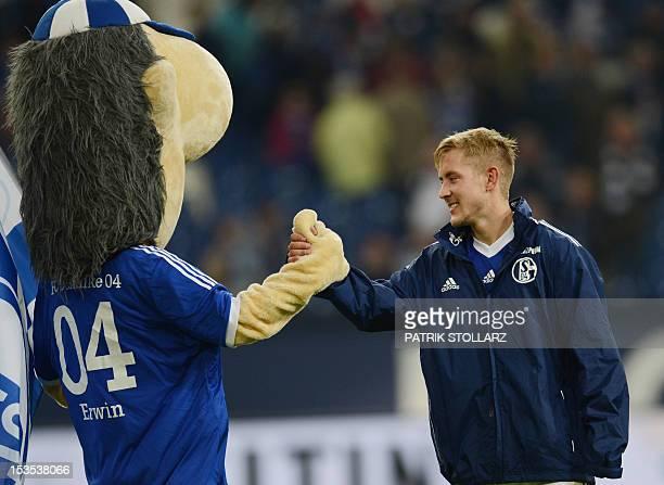 Schalke's midfielder Lewis Holtby and mascot Erwin celebrate after the German first division Bundesliga football match FC Schalke 04 vs VfL Wolfsburg...