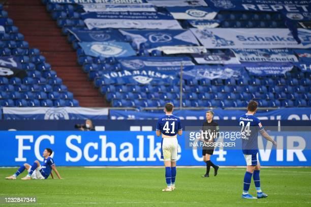 Schalke's players react after the German first division Bundesliga football match FC Schalke 04 v Hertha Berlin on May 12, 2021 in Gelsenkirchen,...