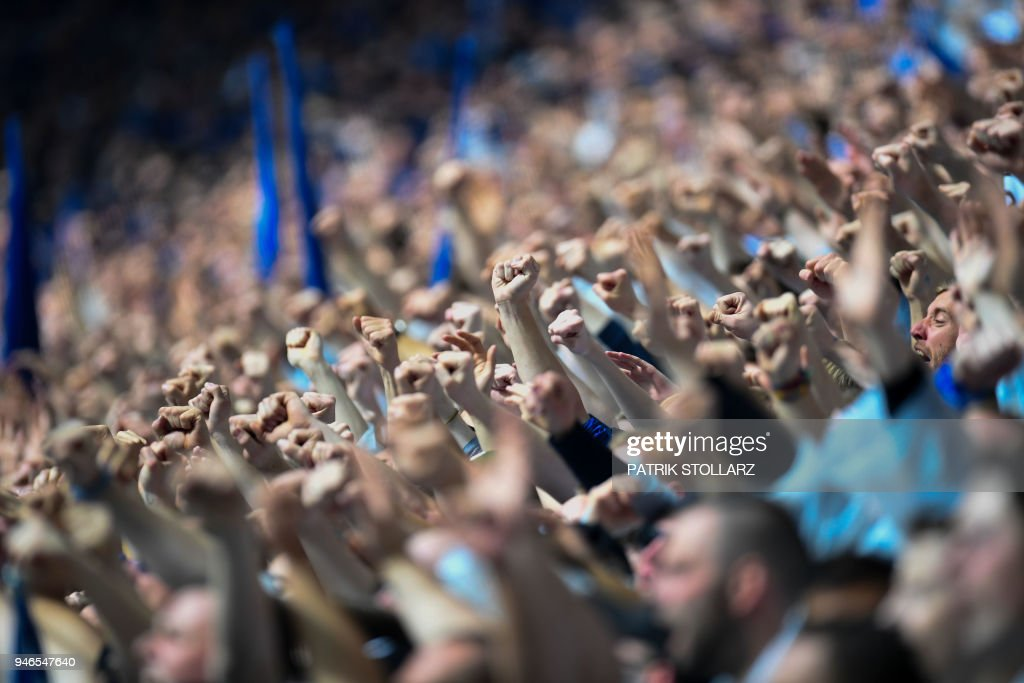 Schalke's supporters celebrate during the German first division Bundesliga football match FC Schalke 04 vs Borussia Dortmund, in Gelsenkirchen, western Germany, on April 15, 2018. / AFP PHOTO / Patrik