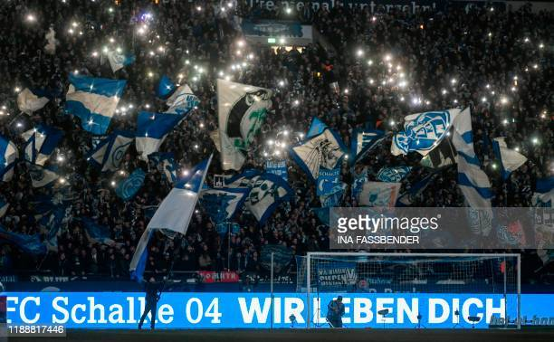 TOPSHOT Schalke's supporters wave their flags before the German first division Bundesliga football match Schalke 04 v Eintracht Frankfurt in...
