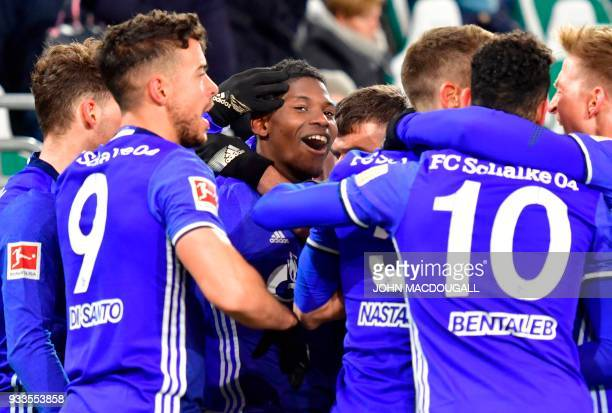 Schalke's Swiss forward Breel Embolo celebrates with Schalke players after an own goal by Wolfsburg during the German First division Bundesliga...