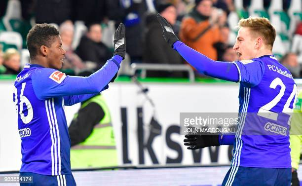 Schalke's Swiss forward Breel Embolo celebrates with Schalke's German defender Bastian Oczipka after an own goal by Wolfsburg's German defender Robin...