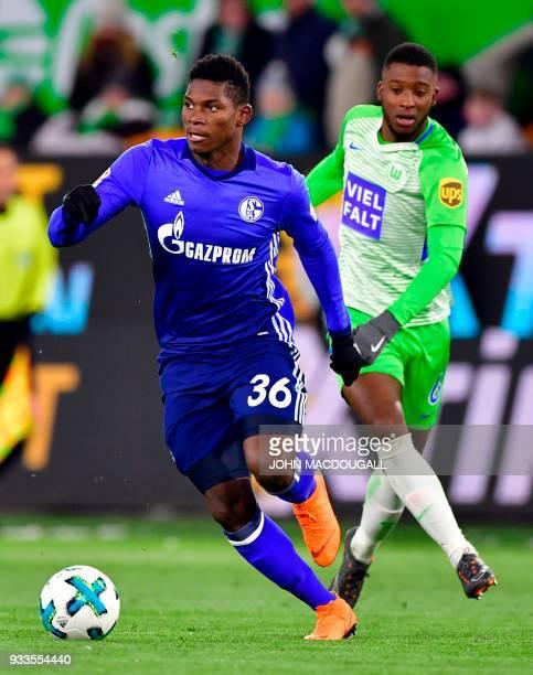 Schalke's Swiss forward Breel Embolo vies with Wolfsburg's Dutch midfielder Riechedly Bazoer during the German First division Bundesliga football...
