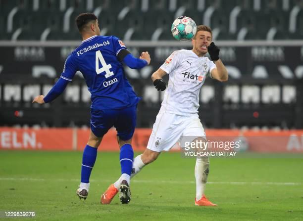 Schalke's Turkish defender Ozan Kabak and Moenchengladbach's German forward Patrick Herrmann vie for the ball during the German first division...