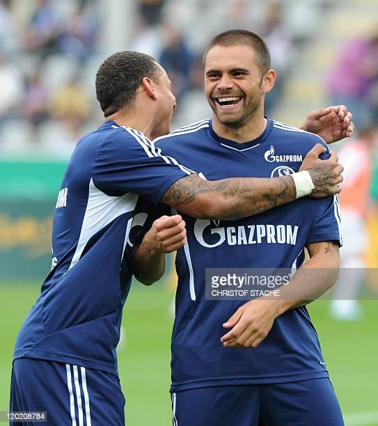Schalke's US midfielder Jermaine Jones and his teammate Brazil striker Edu joke ahead of the German DFB Cup first round football match between FC...