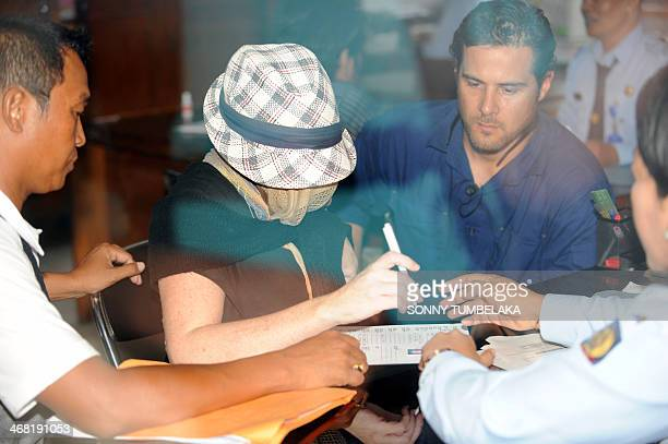 Schapelle Corby signs a form at a correction bureau in Denpasar on Indonesia's resort island of Bali on February 10, 2014. The 36-year-old was...