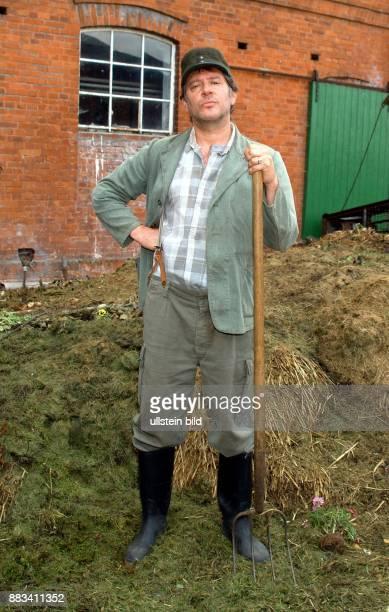 Schauspieler D Ganzkörperaufnahme steht als Kurt Brackelmann in der NDRFamilienserie 'Neues aus Büttenwarder' auf dem Mist