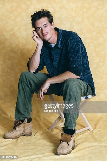 Schauspieler D Porträt sitzt auf einem Hocker undstützt den Kopf auf die Hand August 1999