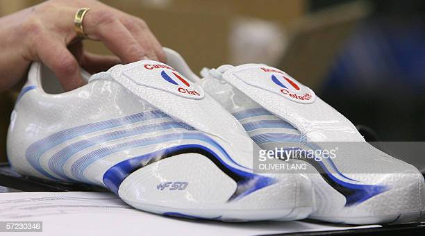 Picture taken 22 March 2006 shows an employee of German sports equipment maker Adidas taking a special edition of the F50 TUNIT football shoe for the...