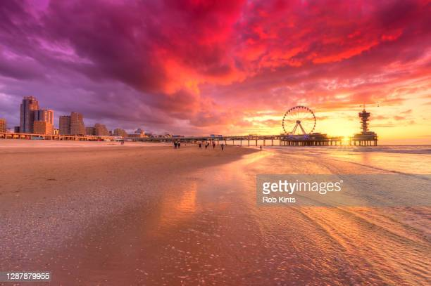 scheveningen pier and ferris wheel at sunset - scheveningen stock pictures, royalty-free photos & images