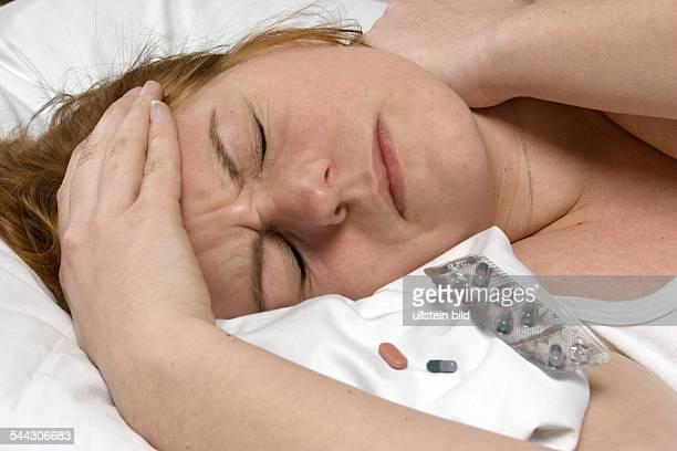 Schlafstörungen Kopfschmerzen Migräne Frau liegt im Bett neben ihr Medikamente