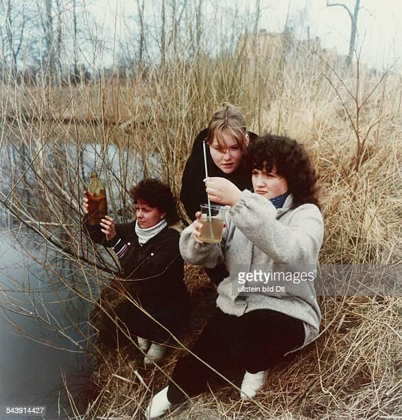 Schülerinnen der 10Klasse einerpolytechnischen Oberschule bei derEntnahme einer Wasserprobe einesMoorteiches bei Stralsund April 1984
