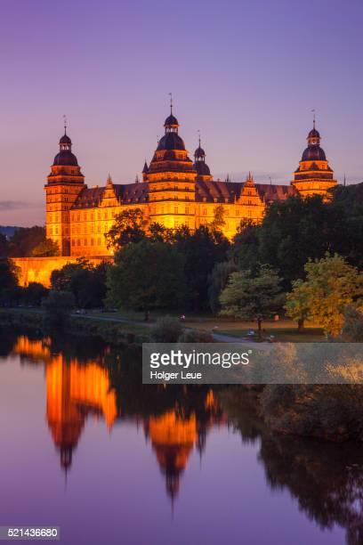 Schloss Johannisburg Palace and parklands along Main river at dusk