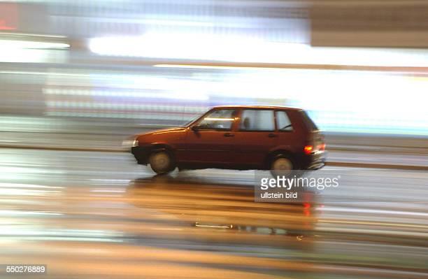 Schnell fahrendes Auto auf regennasser Fahrbahn