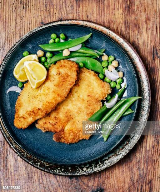 schnitzel with green peas - breaded stock photos and pictures