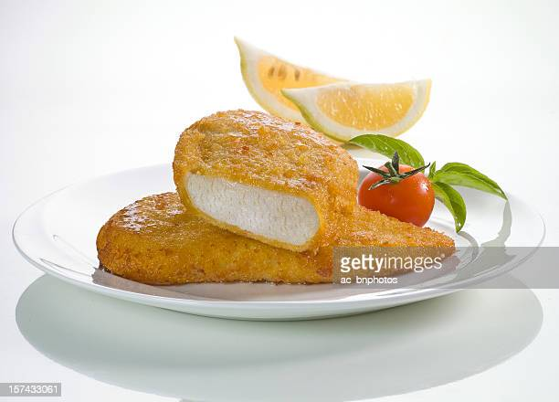 Schnitzels on a plate with cherry tomato and basil