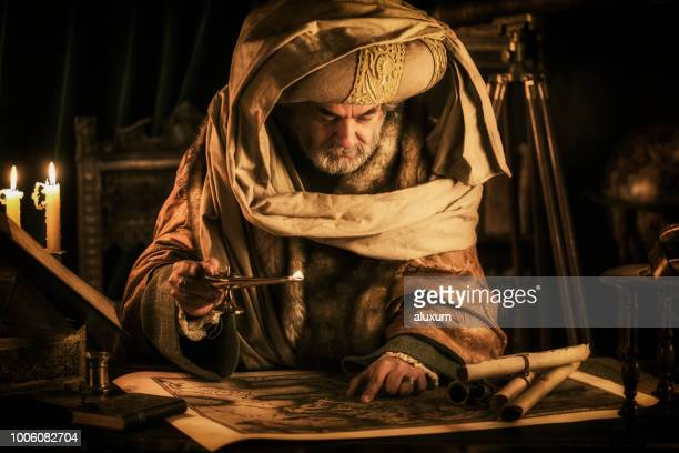 scholar looking at old map - antiquities stock pictures, royalty-free photos & images