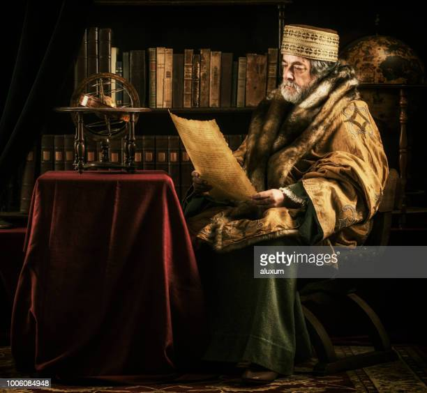 scholar with armillary sphere reading old parchment document - ancient stock pictures, royalty-free photos & images