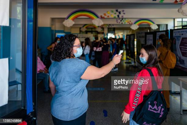 Scholastic collaborator of the Higher Institute Mons. Antonio Bello in Molfetta measures the temperature of students on the first day of school in...