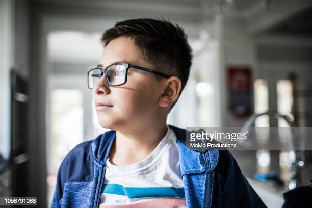 school age boy looking out window - 11 stock pictures, royalty-free photos & images