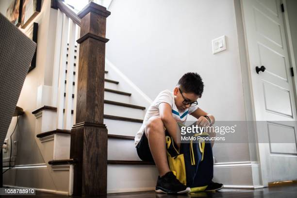 school age boy looking through backpack - shorts stock pictures, royalty-free photos & images