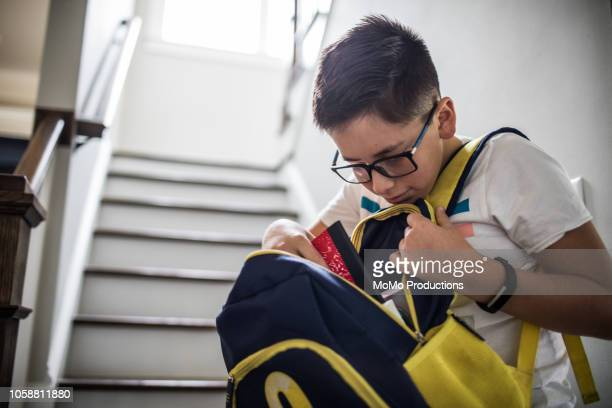 school age boy looking through backpack - rucksack stock pictures, royalty-free photos & images