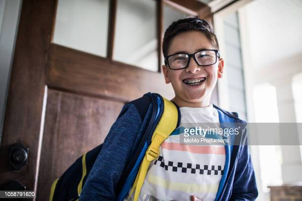 school age boy smiling and leaving for school - 10 11 jaar stockfoto's en -beelden