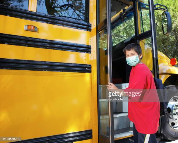 school age boy wearing surgical mask - school bus stock pictures, royalty-free photos & images