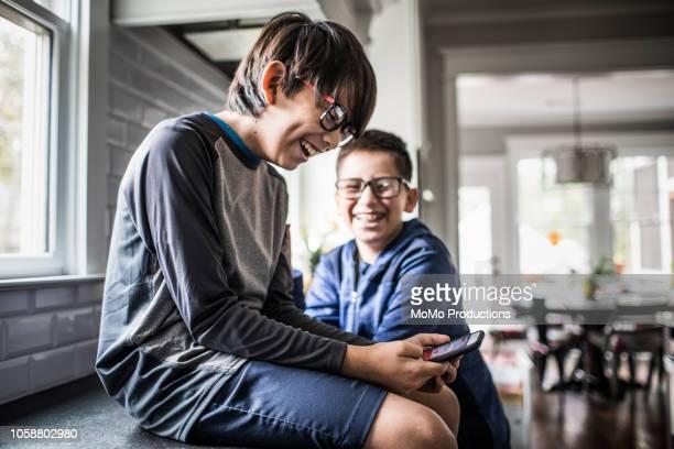 school age boys playing with smartphones - schulkind nur jungen stock-fotos und bilder
