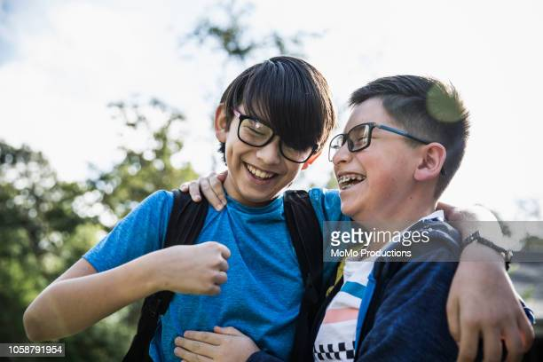 school age brothers laughing outdoors - pre adolescent child stock pictures, royalty-free photos & images