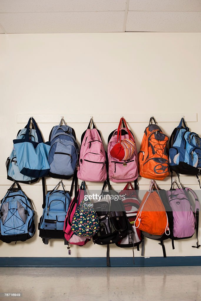 School Backpacks Hanging On Wall Hooks Stock Photo