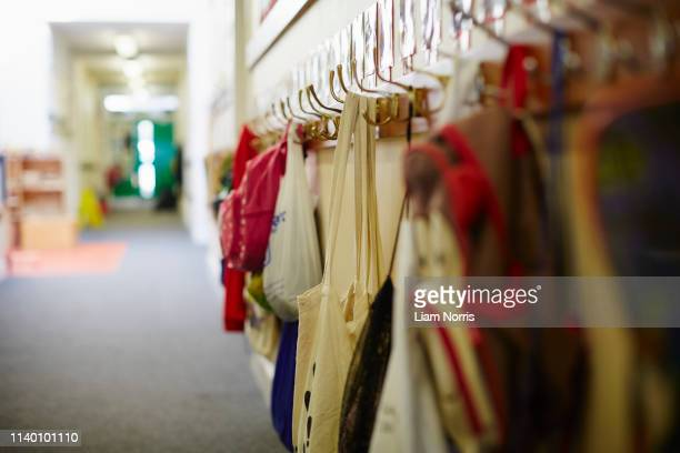 school bags hanging on row of coat hooks in elementary school - shoulder bag stock pictures, royalty-free photos & images